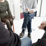 People sitting in a circle discussing 12- step programs