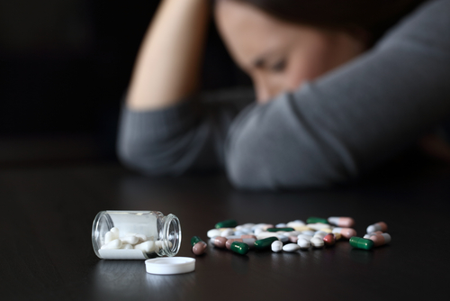 woman and Restoril pills on a counter
