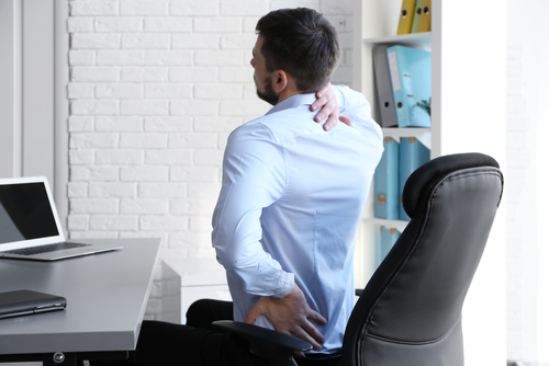 Man in office chair wth back pain