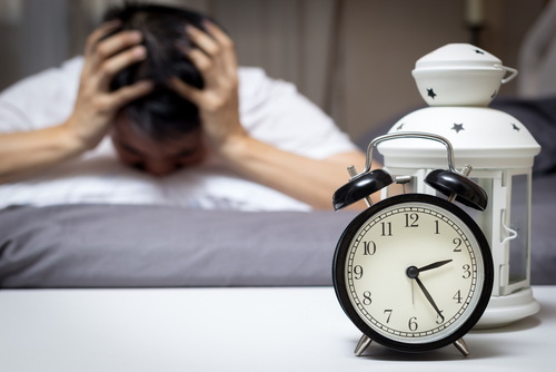 Sleepless man by his nightstand
