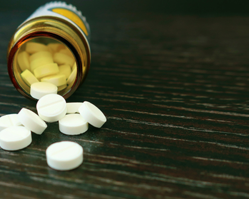 pills-spilling-out-of-bottle-on-a-wooden-surface