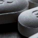 white tablet pills on grey background
