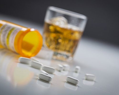 white-tablet-pills-spilling-out-of-prescription-bottle-with-glass-of-alcohol-on-table