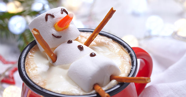 A marshmallow man in a cup of hot chocolate