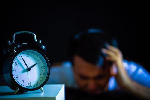 frustrated man next to alarm clock