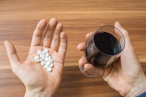 Wine and pills in each hand